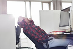 Side view of young businessman relaxing at computer desk in office Stock Image