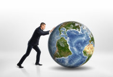 Side view of young businessman rolling the Earth isolated on white background Stock Images