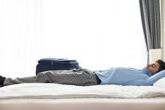 Side view of young businessman sleeping in hotel room Stock Photo