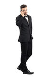 Side view of young businessman in suit walking and talking on the mobile phone turning head to camera Stock Photos