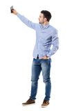 Side view of young businessman taking selfie photo with mobile phone. Full body length portrait isolated over white background royalty free stock photo