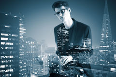 Side view of young businessman using laptop on abstract city background. Royalty Free Stock Photography