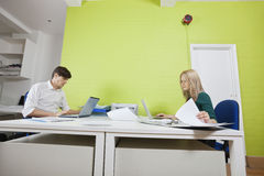 Side view of young businesspeople busy working in office Stock Photo