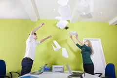 Side view of young businesspeople throwing documents in office Stock Photos