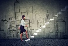 Woman walking up career ladder stock images