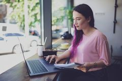 Side view of young businesswoman sitting at table in coffee shop royalty free stock photography