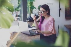 Side view of young businesswoman sitting at table in coffee shop royalty free stock photos