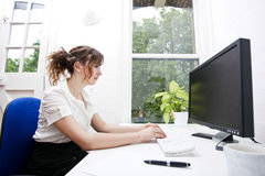 Side view of young businesswoman using computer at desk Royalty Free Stock Photography
