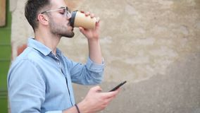 Side view of a young casual man drinking coffee while using phone. Side view of a young casual man drinking coffee while using and texting on a phone and walks stock video footage