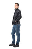 Side view of young casual man with hands in leather jacket pockets looking up serious. Royalty Free Stock Photography