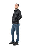 Side view of young casual man in jeans and leather jacket smirking at camera Royalty Free Stock Images