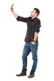 Side view of young casual man in jeans and shirt taking selfie with cellphone. Stock Images