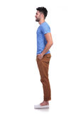 Side view of a young casual man standing in line Stock Photo