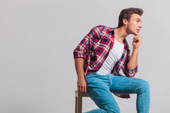 Side view of a young casual man thinking while sitting Royalty Free Stock Photos
