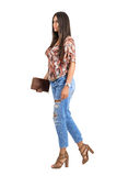 Side view of young casual woman wearing jeans holding purse walking. Royalty Free Stock Images