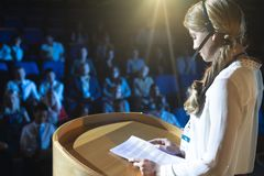 Businesswoman in headset giving presentation in the auditorium. Side view of young Caucasian businesswoman in headset giving presentation in the auditorium royalty free stock photo