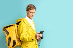 Side view on young caucasian delivery man in yellow unifrom