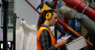 Side view of young caucasian female worker checking stocks in factory 4k stock footage