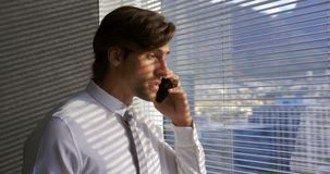 Side view of young Caucasian male executive talking on mobile phone near window in modern office 4k. Side view of young Caucasian male executive talking on stock footage