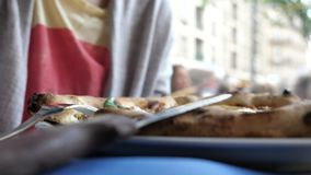 Side view of woman eating pizza in Italian authentic restaurant. Side view of young Caucasian woman tasting delicious pizza in authentic Italian restaurant with stock video footage