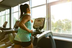 Side view of Young concentrated sports woman running on treadmill stock images