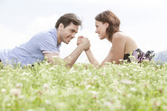 Side view of young couple arm wrestling while lying on grass against sky Royalty Free Stock Photo