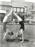 Side view of young couple doing handstands in yard Stock Photos