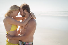 Side view of young couple embracing at beach Stock Photo