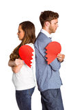 Side view of young couple holding broken heart. Over white background Stock Images
