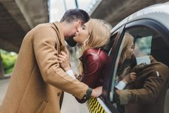 Side view of young couple kissing girl sitting in taxi and man. Standing on street royalty free stock photo