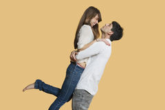 Side view of young couple looking at each other while man carrying girlfriend over colored background Stock Image