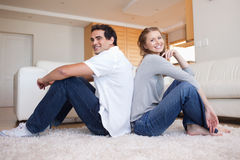 Side view of young couple sitting on the floor back-to-back. Side view of smiling young couple sitting on the floor back-to-back Stock Photos