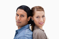Side view of young couple standing back to back Royalty Free Stock Photo
