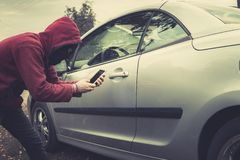 Side view of young criminal in black balaclava and hoodie holding smartphone and trying to interact with car by mobile. Application. Unknown person tries to get royalty free stock image