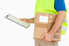 Side view of young delivery man with delivery note Stock Photos