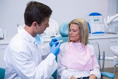 Side view of young doctor showing dental mold to patient Stock Images