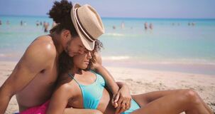 Couple embracing and relaxing on beach. Side view of young ethnic couple sitting and lying while relaxing on sandy beach at the sea in sunny day stock video footage