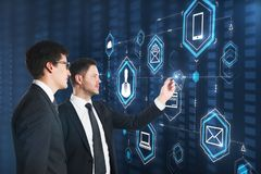 Teamwork and future concept. Side view of young european businessmen using digital business interface on blurry background. Teamwork and future concept stock image