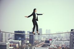 Equilibrium and challenge concept. Side view of young european businesswoman balancing on city and sky background. Equilibrium and challenge concept stock photo