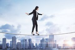 Equilibrium and leadership concept. Side view of young european businesswoman balancing on city and sky background. Equilibrium and leadership concept royalty free stock photo