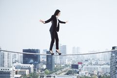 Equilibrium and risk concept. Side view of young european businesswoman balancing on city and sky background. Equilibrium and risk concept stock images