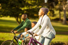Side view of a young family doing a bike ride Royalty Free Stock Photography