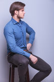 Side view of a young fashion man sitting Royalty Free Stock Photos