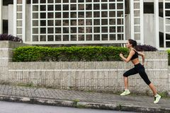 Side view of young female runner listening to music and jogging on sidewalk in town stock images