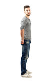 Side view of young fit guy in jeans and sneakers. Looking at camera. Full body length portrait isolated over white background Stock Photography