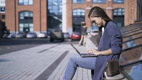 Side view of a young girl with a laptop in the street. Side view of a young girl wearing a blue coat and sunglasses sitting with a laptop in the street and stock video