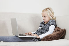 Side view of young girl using laptop on sofa Royalty Free Stock Images