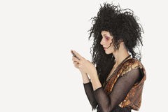 Side view of young Goth woman with teased hair texting on mobile phone over gray background Stock Images