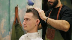 Side view of young handsome caucasian man with piercing in his ear getting his hair dressed and styled by a bearded. Barber in a retro stylish barber shop stock video