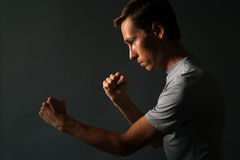 Side view of young handsome man making punches. Low key photography. Stock Photo